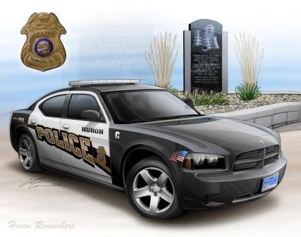This is a photo of a Police Car, police badge, and fallen officer memorial
