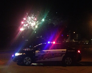Thisi s a photo of a Patrol car with fireworks in the background